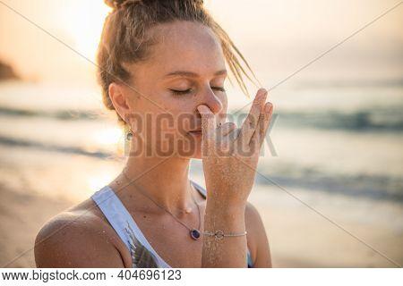 Woman's Face Close Up. Yogi Woman Practicing Nadi Shodhana Pranayama, Alternate Nostril Breathing. B