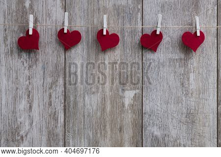 Red Hearts With Clothespins On A Leash Hung In Front Of Rustic Wooden Background With Text Space As