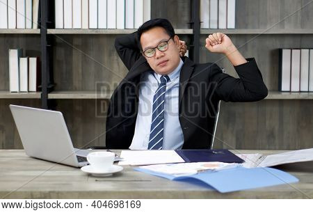 A Businessman In A Suit Stretches Lazily While Looking At A Computer Screen. To Alleviate Pain From