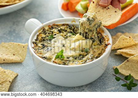 Artichoke Spinach Dip In A Baking Dish With A Cheese Pull