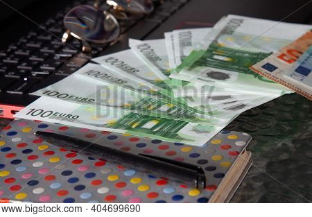 Notebook, Glasses, Scattered Euro Banknotes And A Black Pen On A Laptop Keyboard. Copywriting, Writi
