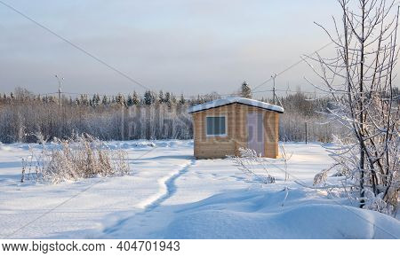 Wooden House At Edge Of Forest. One-storey Cottage In Winter Weather. Single Private House Near Fore