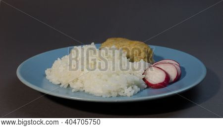 Boiled White Rice With Fish Cutlet Wrapped In Bacon On A Gray Background Blue Plate. Baked Fish Meat