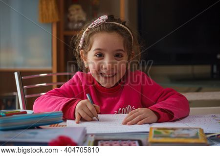 Smiling 6 Year Old Girl Does Her Homework, On The Table The Case With The Colors And Pens