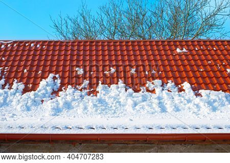 Snow Melts From The Roof Of The House On A Spring Day. Danger Of Avalanches From Roofs. Snow Removal