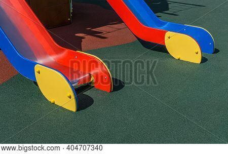 Two Wooden Chutes Of Slides Are On Playground With Coating Crumb Rubber. Sunny Day. Copy Space