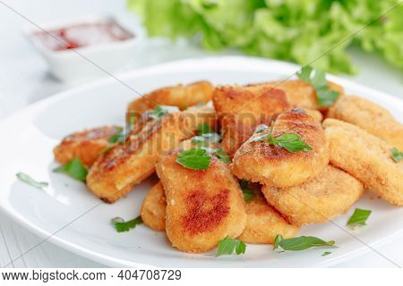 Nuggets On A White Plate. Fried Chicken Nuggets With Ketchup Sprinkled With Chopped Parsley.