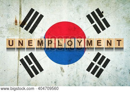 Unemployment. The Inscription On Wooden Blocks On The Background Of The Korea Flag. Unemployment Gro
