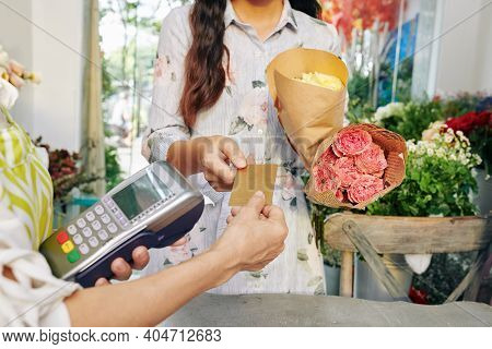 Young Woman With Flower Bouquets Giving Credit Card To Florist With Paying Terminal In Shop