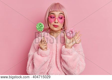 Thoughtful Female Sweettooth In Trendy Sunglasses Looks At Tasty Donut Holds Candy On Stick Dressedi