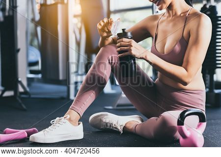 Sport Woman Workout At Fitness Center With Relax And Taking A Break Beautiful Girl Drinking Protein