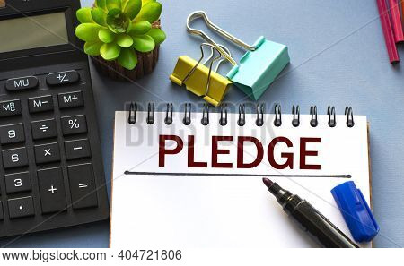 Pledge Word Is Written In A Notebook With A Marker, Calculator, Clamps And Cactus. Business Concept