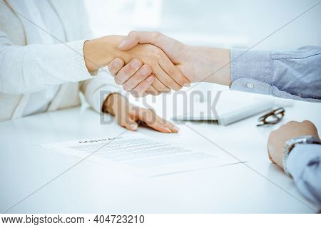 Casual Dressed Businessman And Woman Shaking Hands After Contract Signing In White Colored Office. H