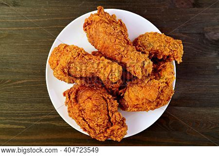 Plate Of Delectable Golden Brown Crispy Fried Chickens On Wooden Background
