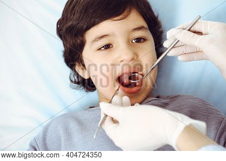 Cute Arab Boy Sitting At Dental Chair With Open Mouth During Oral Checking Up With Doctor. Visiting