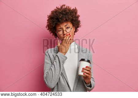 Tired Sleepy Dark Skinned Woman Covers Mouth And Yawns Holds Takeaway Coffee Has Exhausted Look Dres