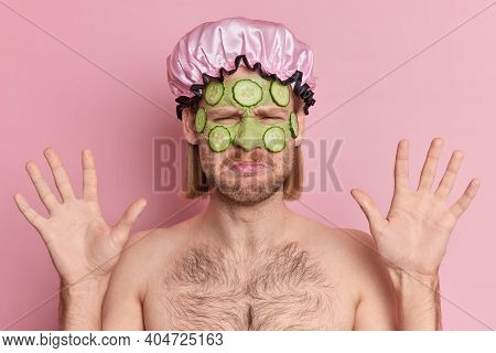 Upset European Man Applies Green Cucumber Mask Raises Hands Has Dissatisfied Expression Reacts On So