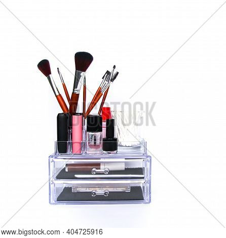 Organised Collection Of Makeup Brushes, Lipsticks And Other Tools In Plastic Storage.