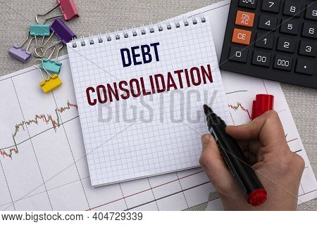 A Woman's Hand Writes In A Notebook The Words Debt Consolidation On The Background Of A Graph, Calcu