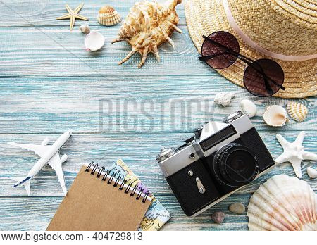 Summer Travel Concept. Old Film Camera, Hat, Shell And Palm Leaves On Blue Wooden Background.