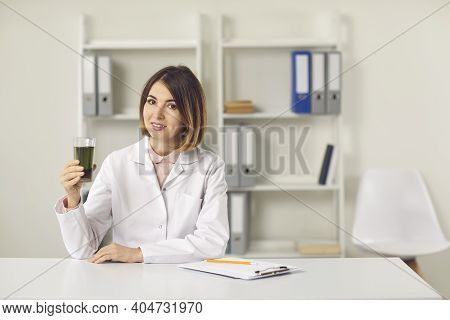 Young Woman Nutritiologist Holding Glass Of Green Chlorophyll Spirulina Drink