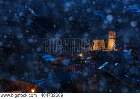Night View Of Church In Champagny-en-vanoise Village In France During Heavy Snowfall At Winter