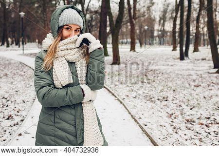 Winter Fashion. Young Woman Wearing Long Green Coat With Scarf, Hat, Mittens In Snowy Park. Modern C