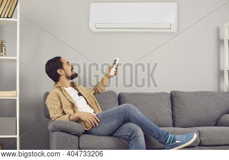 Young Man Sitting On Sofa At Home And Turning On Air Conditioner With Remote Control