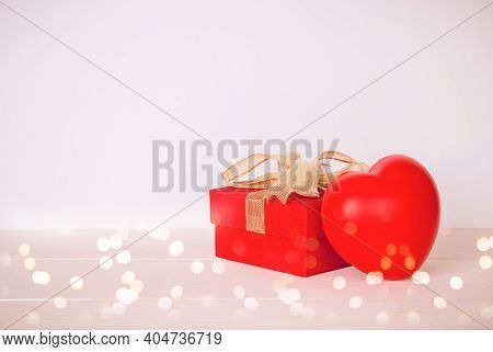 Red Gift Box And Heart Shape On Wooden Table With Bokeh Background, Love And Romance, Presents In Ce