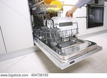Integrated Dishwaher Machine Loading. Female Hand Puts Plates In Dishwasher Standing In A Modern Kit