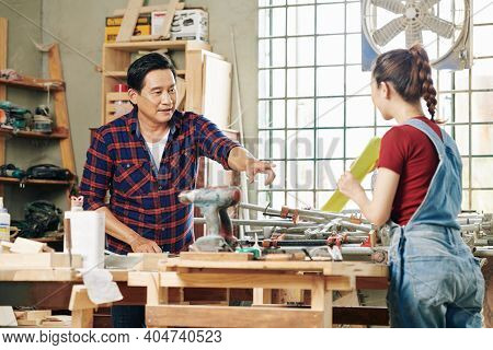 Carpenter Asking Female Apprentice To Show Him Document With Furniture Draft