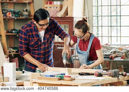 Experienced Carpenter Showing Female Apprentice How To Drill Wooden Planks