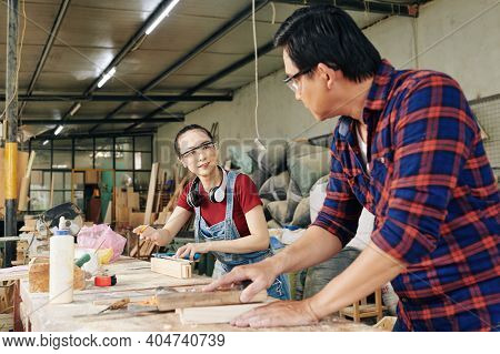 Female Carpenter Asking Experienced Colleague To Help Her With Advice On Making Even Planks For Furn