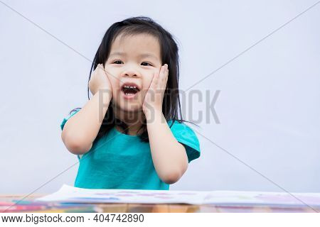 Child Showed A Surprised Expression And Sweet Smile. Children Raised Both Hands And Held Her Cheek.