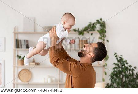 Happy Father Playing With Baby Toddler Holding Child Above Head Cuddling And Bonding Standing At Hom