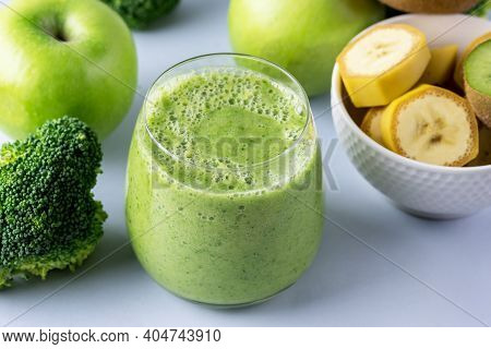 Glass Of Green Healthy Smoothie With Banana Broccoli Green Apples Blue Background Close Up Above Hor