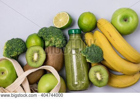 Glass Bottle Of Green Healthy Smoothie With Banana Broccoli Green Apples Lime And Kiwi Blue Backgrou