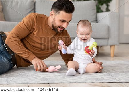 Young Dad Playing With Little Baby Toddler Holding Toys Enjoying Time Together, Bonding Sitting On F