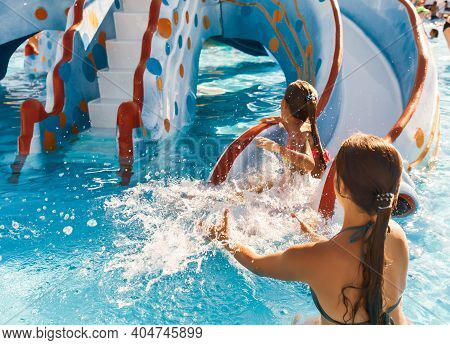 The Cautious Older Sister Catches Her Cute Little One Who Slides Down The Slide Right Into The Pool