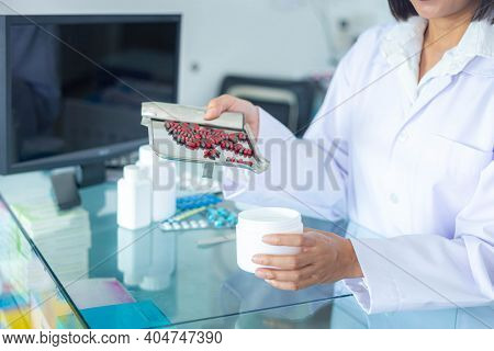 The Pharmacist Is Pouring The Medicine From Stainless Steel Tray Into The White Medicine Bottle. Hea