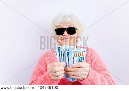 Blonde Old Lady Wear Pinl Sweater And Sunglasses Showing Money Isolated White Background