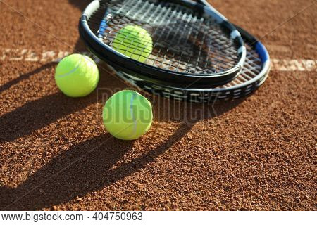 Tennis Balls And Rackets On Clay Court