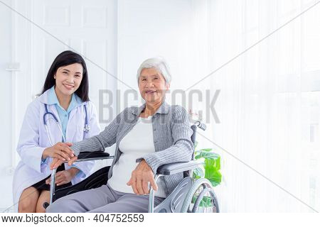 Happy Senior Woman Sitting On Wheelchair, A Young Nurse Taking Care Of A Disabled Elderly Woman, Sen