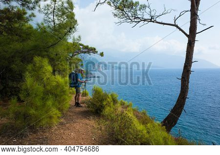 Hiking on Lycian way. Man with backpack enjoys view blue sea water of Mediterranean coast under coniferous trees on Lycian Way trail, Turkey