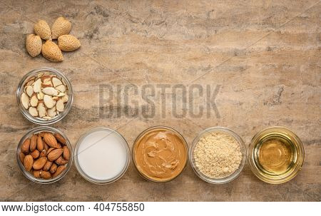 collection of almond super foods: nuts, flour, slices, milk, oils and butter - top view of small glass bowls over textured bark paper with a copy space