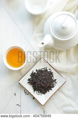 Finest quality blended tea powder. Black tea leaves and refreshing tea filled in a cup along with white tea pot. View from above.