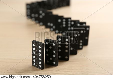 Black Domino Tiles With White Pips On Wooden Table
