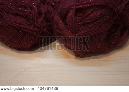 Red Yarn Thread On Yellow Background. Shaped Woolen Yarn Color Red And Knitting Needles.
