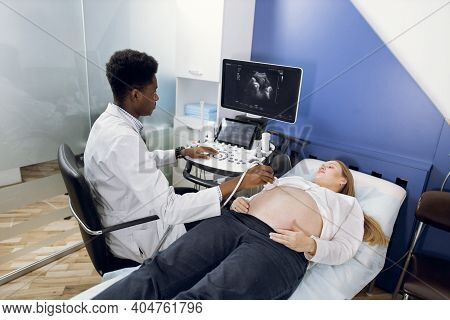 Ultrasound Of Pregnancy. Young Focused High-skilled African Male Doctor, Performing Examination Of P