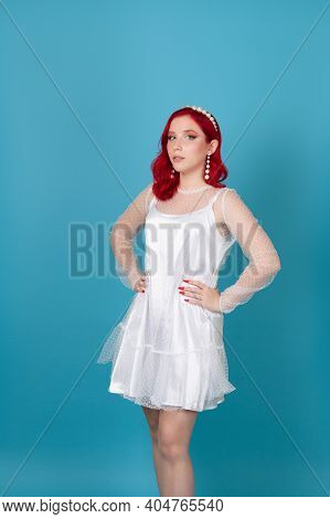 Slender Arrogant Self-confident Young Woman With Red Hair And Hands On Waist In White Silk Mesh Dres